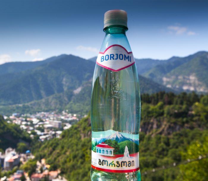 """фото щелочной минеральной воды """"Боржоми"""" на фоне горного селения"""