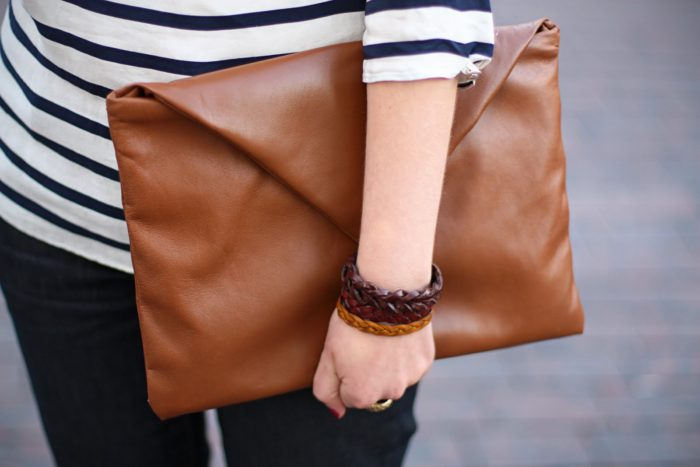 коричневый клатч-конверт в руках у девушки