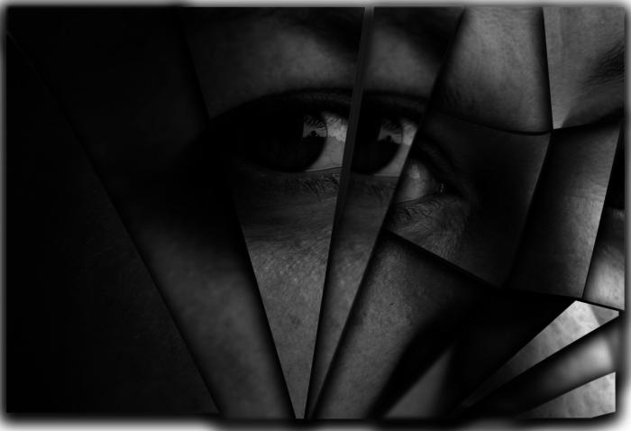 крупные трещины на зеркале и отражение человека в нём