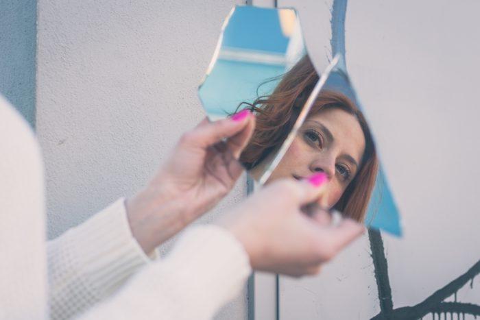 девушка держит в руках 2 крупных осколка разбившегося зеркала