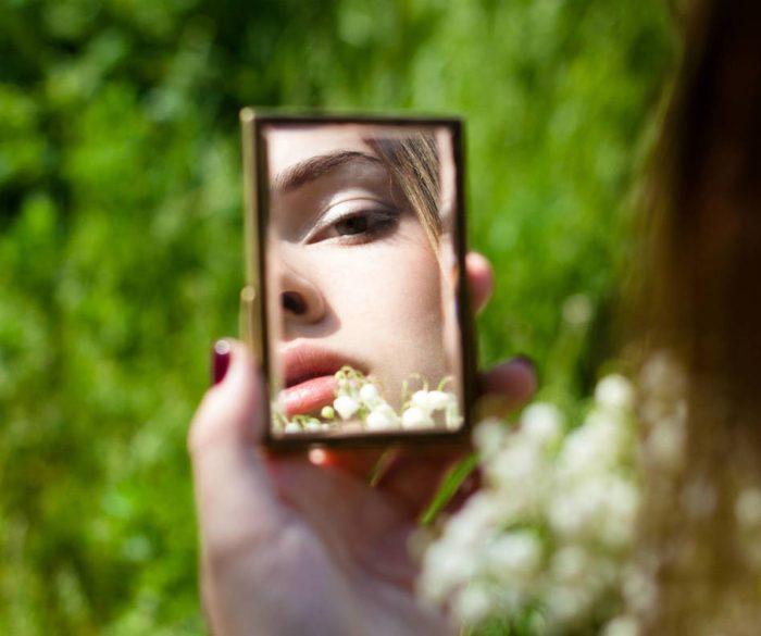 девушка смотрит в зеркальце и проверяет его на отсутствие сколов