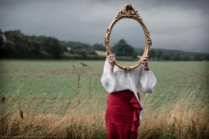 фото девушки с зеркалом, которое упало, но осталось целым
